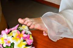 Pés do ` s da noiva perto das flores foto de stock