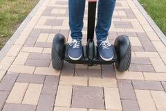 Pés do ` s da pessoa nas sapatilhas que rolam no 'trotinette' do giroscópio em pavimentar a estrada imagens de stock