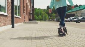 Pés do ` s das mulheres que montam em patins de rolo na rua da cidade filme