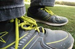 Pés do ` s do menino na grama que senta-se apenas em sapatas vestindo do esporte do parque imagens de stock
