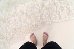 Pés do ` s dos homens na praia Fotografia de Stock