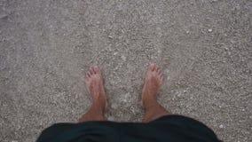 Pés do ` s dos homens na praia do mar de adriático e das ondas do mar no por do sol vídeos de arquivo