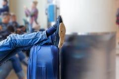 Pés do ` s dos homens nas calças de brim em um saco com bagagem em um fundo borrado na sala de espera para partidas no aeroporto, Imagem de Stock