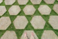 Pés do selfie com os pés do turista que estão em um gramado decorado pelas lajes e pela grama de pedra Ajardinar em Ásia Imagem de Stock Royalty Free