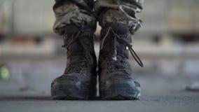 Pés do soldado nas botas velhas que fazem uma etapa para a frente no assoalho concreto sujo empoeirado em uma construção abandona filme