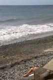 Pés do sunbather na praia Imagem de Stock