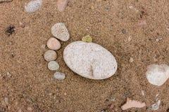 Pés do traço feitos de um fim da pedra do seixo acima no deser da areia do mar Fotos de Stock
