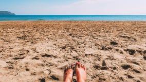 Pés do ` um s da mulher na areia em uma praia fotografia de stock