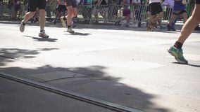 Pés dos corredores de maratona que correm ao longo do asfalto vídeos de arquivo