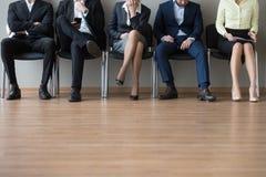 Pés dos empresários que sentam-se na cadeira na entrevista de trabalho da espera da fila fotografia de stock royalty free