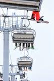 Pés dos esquiadores e dos snowboarders que montam em um elevador de cadeira do cabo no fim cênico do vertical das montanhas nevad Fotografia de Stock