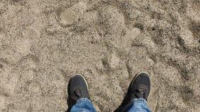 Pés dos homens nas sapatilhas na areia filme