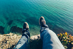 Pés dos homens nas sapatilhas no fundo do conceito de relaxamento landscapehiking do curso do mar pitoresco imagem de stock