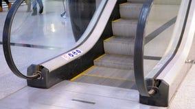 Pés dos povos que movem sobre um elevador da escada rolante no shopping video estoque