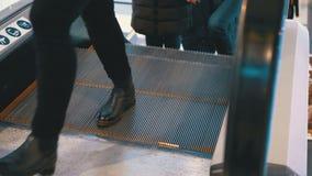 Pés dos povos que movem sobre um elevador da escada rolante no shopping filme