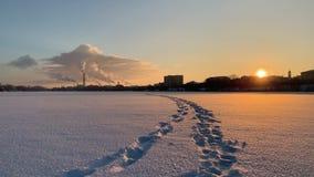 Pés dos traços com paisagem industrial do inverno sobre a cidade coberto de neve no por do sol vídeos de arquivo