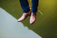 Pés e botas de um homem novo sobre o lago com reflexão imagem de stock royalty free