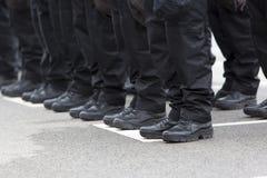 Pés e botas dos polícias fotografia de stock