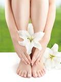 Pés e braços despidos fêmeas com lírios brancos Imagens de Stock