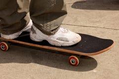 Pés e equitação do patim em um skate Imagem de Stock