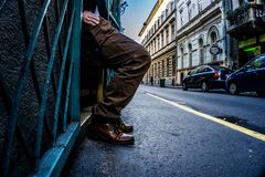Pés e mão de um homem que alcança em seu bolso nas ruas de Budapest, Hungria com as linhas principais que empasizing o ato imagem de stock