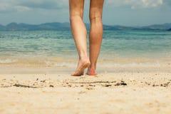 Pés e pés da jovem mulher que andam na praia Imagens de Stock
