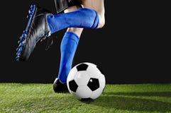 Pés e pés do jogador de futebol na ação que corre e que pinga com a bola que joga na grama verde Imagem de Stock