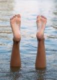 Pés e pés fêmeas upside-down na água fotografia de stock royalty free