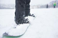 Pés e placa de um snowboarder Imagem de Stock