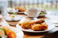 Pés e salada fritados friáveis do cilindro da galinha na tabela de jantar, c fotografia de stock royalty free