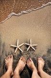 Pés e starfishes Foto de Stock