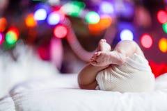 Pés e tecido recém-nascidos do bebê com árvore de Natal e luzes coloridas da festão foto de stock royalty free