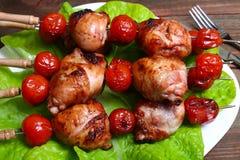 Pés e tomates grelhados de galinha do no espeto do assado em espetos Imagens de Stock