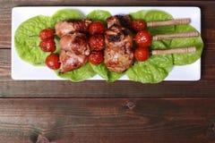 Pés e tomates grelhados de galinha do no espeto do assado em espetos Imagens de Stock Royalty Free
