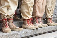 Pés em botas bege do exército dos calçados da cor da areia Imagem de Stock