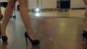 Pés em calçados pretos à moda, close-up das sapatas nas mulheres que vão ao longo da passarela, sapatas dos pés das coleções na s video estoque