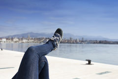 Pés em calças das calças de brim e em sapatas azuis do esporte na costa de mar Imagem de Stock Royalty Free