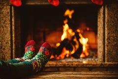 Pés em peúgas de lã pela chaminé A mulher relaxa por morno Fotos de Stock Royalty Free