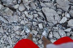Pés em sapatas do esporte e short vermelho no trajeto rochoso nas montanhas foto de stock