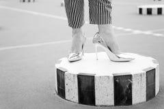 Pés em sapatas douradas em coluna listrada em Paris, france Fotos de Stock Royalty Free