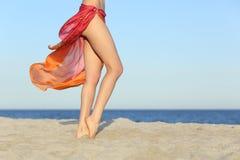 Pés eretos da mulher que levantam na praia que veste um pareo fotografia de stock royalty free