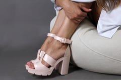 Pés fêmeas bonitos nas sandálias brancas da plataforma da forma Fotografia de Stock