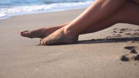 Pés fêmeas bonitos que encontram-se na areia e que relaxam perto da costa de mar Jovem mulher que senta-se na costa e que bronzea filme