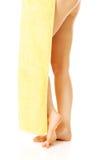 Pés fêmeas cobertos com uma toalha amarela Foto de Stock