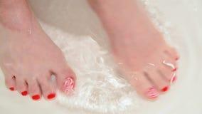 Pés fêmeas com laca vermelha em pregos na banheira com água video estoque
