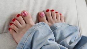Pés fêmeas com laca vermelha em pregos no sofá filme