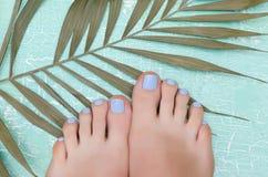 Pés fêmeas com pedicure azul Imagens de Stock