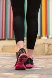 Pés fêmeas das sapatilhas do close up Imagem de Stock