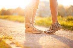 Pés fêmeas e masculinos com as sapatas à moda no por do sol Amores dos pares fotos de stock royalty free
