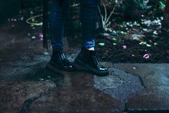 Pés fêmeas em botas altas da pintura no fundo, concreto molhado, sapatas da forma Imagens de Stock Royalty Free